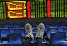 An investor puts his feet onto the back of a chair in front of an electronic board displaying stock information at a brokerage house in Hefei, Anhui province October 26, 2012. REUTERS/Stringer