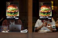 Customers sitting inside a fast food shop are seen behind its hamburger advertisement poster on a window at the Tokyo's Akihabara shopping district, Japan, May 19, 2015. REUTERS/Yuya Shino