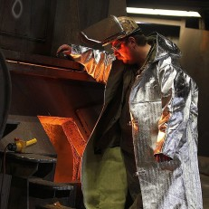 A steel worker stands next to a smelting furnace in Duisburg, Germany on May 21st 2015. Credit: EPA