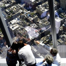 Visitors look out over New York city streets from the One World Observatory at One World Trade Center, May 29th 2015. The observatory is on floors 100 to 102 of the building and allows panoramic views of the city. Credit: EPA