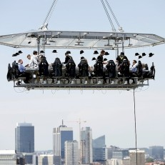 Guests enjoy a 'Dinner in the Sky' on a platform hanging in front of the Cinquantenaire Park, Brussels, Belgium on June 5th 2015. 'Dinner in the Sky' accommodates 22 guests, seated at a table suspended from a crane at a height of 40 metres (131 feet). Credit: Reuters
