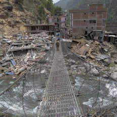 Local residents walk across a bridge linked to buildings damaged by the Nepalese earthquakes in Singati, Nepal on May 15th 2015. Credit: Reuters