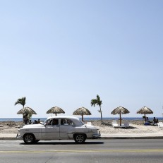 A vintage car passes people enjoying an artificial beach at the Malecón, Havana, Cuba on May 21st 2015. The beach is a four-mile art installation called 'Behind the Wall' and is part of the Havana Biennial Art Fair which runs from May 22nd 2015.
