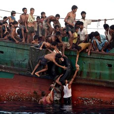 Rohingya migrants pass food supplies dropped by a Thai army helicopter to others aboard a boat drifting in the Andaman sea off the southern island of Koh Lipe, Thailand on May 14th 2015. A boat crammed with scores of Rohingya migrants, including many young children, was found drifting in Thai waters with passengers saying several people had died over the last few days. Credit: AFP