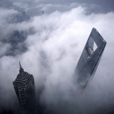 The Shanghai World Financial Centre (right) and the Jin Mao Tower are seen during heavy rain at the financial district of Pudong in Shanghai, May 15th 2015. Credit: Reuters