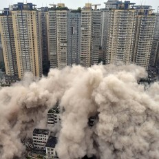 Old residential buildings are demolished by a controlled blast in Chongqing municipality, China on June 16th 2015. The buildings were demolished in five seconds in order to make way for the construction of a future traffic hub. Credit: Reuters