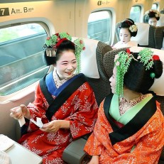 """Apprentice geisha, or """"maiko"""", from Japan's ancient capital Kyoto, travel to Tokyo on the Shinkansen train line, June 21st 2015. Some 40 maiko performed traditional dances in Tokyo for the Kyoto travel campaign. Credit: AFP"""