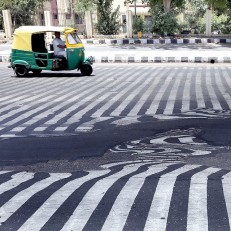Road markings appear distorted as the asphalt starts to melt due to the high temperature in New Delhi, India, May 27th 2015. More than 1,150 people are reported to have died due to the heatwave sweeping across southern India. Credit: EPA