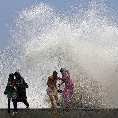 Indian girls enjoy high tide waves marking the arrival of monsoon season on the Arabian Sea coast in Mumbai, India, June 16th 2015. The annual monsoon rains which usually hit India from June to September are crucial for farmers whose crops feed hundreds of millions of people. Credit: AP