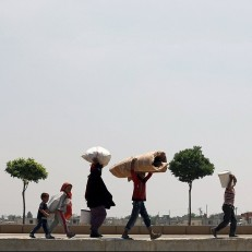 Syrian refugees walk to the Akcakale border gate in Sanliurfa province, Turkey to return to their homes in the northern Syrian town of Tel Abyad on June 17th 2015. The border town of Tal Abyad has been liberated from the Islamic State (IS) group. Kurdish forces took the strategic town after several days of intense fighting, which sparked the exodus of thousands of refugees into neighbouring Turkey. Credit: Reuters