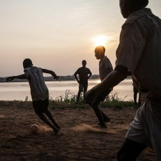 Boys play football in Dongo, a small village on the shore of the Ubangui river, north western region of Democratic Republic of Congo, June 24th 2015. Credit: AFP