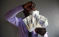 Un hombre muestra varios dólares zimbabuenses, en Harare (Zimbabue). El presidente zimbabuense, Robert Mugabe, ha pedido que los dólares zimbabuenses sean devueltos al Banco Central del país para ser cambiados por dólares estadounidenses. El gobierno ha anunciado que procederá a la desmonetarización del país despúes de que el dólar zimbabuense haya perdido su valor a causa de la hiperinflación. AARON UFUMELI (EFE)