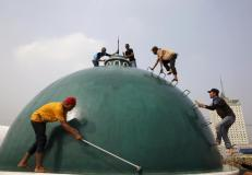 Youths clean a dome of a mosque ahead of the upcoming holy fasting month of Ramadan in Jakarta June 15, 2015. REUTERS/Beawiharta