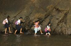 A woman accompanies some students as they wade in the shallow part of a rocky beach to their school to attend the first day of classes in Sitio Kinabuksan, Kawag village, Subic, Zambales Province, north of Manila June 1, 2015. An estimated 24 million public school students in the primary and secondary levels attend the opening of classes nationwide, local media reported. REUTERS/Lorgina Minguito