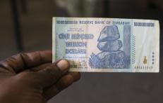 A man holds up for a picture a one hundred trillion Zimbabwean dollar note inside a shop in Harare, Zimbawe, June 12, 2015. The Zimbabwean dollar, ravaged by hyperinflation that peaked at 500 billion percent in 2008, ceased to be legal tender on Friday. REUTERS/Philimon Bulawayo