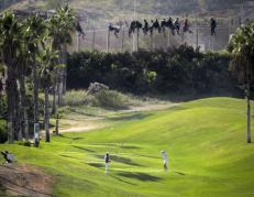 A golfer hits a tee shot as African migrants sit atop a border fence during an attempt to cross into Spanish territories between Morocco and Spain's north African enclave of Melilla October 22, 2014. REUTERS/Jose Palazon