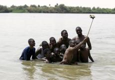 A group of young men use a selfie stick to take a picture of themselves in shallow waters known as the first cataract of the River Nile outside Khartoum, Sudan, May 22, 2015. In Sudan, which faces insurgences in the western region of Darfur and along its border with breakaway South Sudan, as well as double-digit inflation and high unemployment, life goes on for young people in the capital Khartoum. REUTERS/Mohamed Nureldin Abdallah
