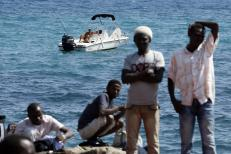 A man fishes from his boat as a group of migrants gather on the seawall at the Saint Ludovic border crossing on the Mediterranean Sea between Vintimille, Italy and Menton, France, June 14, 2015. On Saturday, some 200 migrants, principally from Eritrea and Sudan who attempted to cross the border, were blocked by Italian police and French gendarmes. REUTERS/Eric Gaillard