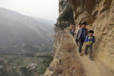 Xu Liangfan escorts students on a cliff path as they make their way to Banpo Primary School in Shengji county, Bijie city in Guizhou province, China, March 12, 2013. REUTERS/Stringer