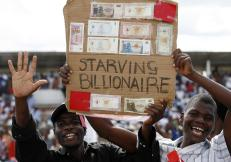 Zimbabwe opposition Movement for Democratic Change supporters show old worthless bank notes at an election rally in Chitungwiza, near the capital Harare, March 27, 2008. REUTERS/Howard Burditt