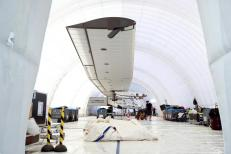 The Solar Impulse 2, a solar powered plane, is parked in an inflatable hangar after an unscheduled landing at Nagoya airport in Japan, June 3, 2015. The solar-powered plane attempting a round-the-world flight will cut short the seventh leg of its 35,000-km global (22,000-mile) journey, landing in Nagoya, western Japan, due to bad weather. REUTERS/Thomas Peter