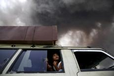 A family sit inside a car as they prepare to leave a danger zone area, as ash spews from Mount Sinabung volcano during an eruption at Tiga Serangkai village in Karo Regency, North Sumatra province, Indonesia June 24, 2015. REUTERS/Beawiharta