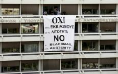 Employees of the Ministry of Finance and National Economy stand by a banner unfolded from a balcony of the Finance Ministry in Athens, Greece, July 1, 2015. REUTERS/Jean-Paul Pelissier