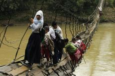 Students hold on to the side steel bars of a collapsed bridge as they cross a river to get to school at Sanghiang Tanjung village in Lebak regency, Indonesia's Banten village, January 19, 2012. REUTERS/Beawiharta