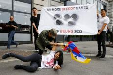 Tibetan protesters hold a banner outside the Beijing 2022 Winter Olympic Candidate City presentation at the Palace hotel in Lausanne, Switzerland, June 10, 2015. The banner reads 'No More Bloody Games' and 'Stop Beijing 2022'. REUTERS/Ruben Sprich