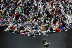 """A child plays next to """"Personnes"""" (Persons), a sculpture made with used clothes, at the Fine Arts Museum in Santiago, Chile November 12, 2014. REUTERS/Ivan Alvarado"""