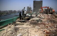 Egyptian workers and a bulldozer destroy concrete during the demolition of the headquarters of former Egyptian President Hosni Mubarak's political party National Democratic Party in Cairo, Egypt, June 1, 2015. REUTERS/Amr Abdallah Dalsh