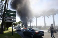 A policeman secures the traffic as taxi drivers, who are on strike, burn tires to block the access to Nice International airport during a national protest against car-sharing service Uber in Nice, France, June 25, 2015. French taxi drivers stepped up protests against U.S. online cab service UberPOP on Thursday, blocking road access to airports and train stations in Paris and other cities. REUTERS/Jean-Pierre Amet