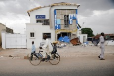 Pedestrians and a cyclist pass a bank, which locals say was looted by Boko Haram. People drive to Mubi, a city about an hour's drive south, to get goods but this vital route will be blocked once the rainy season comes into full swing next month. REUTERS
